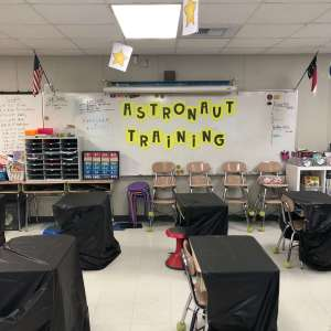 """poster that says """"astronaut training"""" in a space themed classroom"""