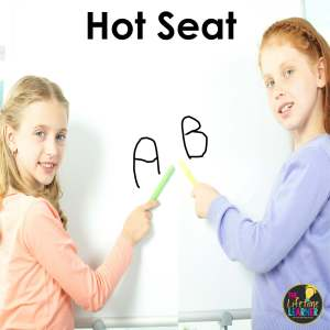 two students pointing to answers on whiteboard