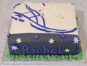 Gâteau 10 pouces à la vanille, crème au beurre meringue suisse et recouvert de fondant. Soulier de course en fondant et fleurs en pastillage.