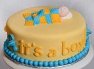 Gâteau de 7 pouces, 2 étages, garni de crème au beurre meringue suisse et recouvert de fondant. Bébé en fondant sur le dessus et décorations en chocolat autour.