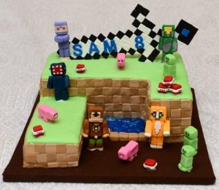 Gâteau de village Minecraft au chocolat avec glaçage meringue Suisse à la vanille vert, recouvert de fondant et personnages + épée en fondant.