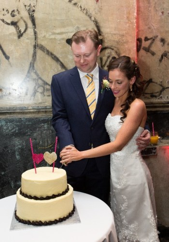 Bride and Groom cutting Cheesecake Shop wedding cake with DIY cake topper at the Brisbane Powerhouse