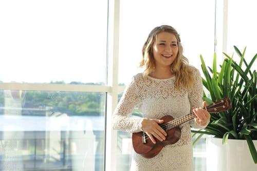 Bride wearing wedding dress and playing ukulele
