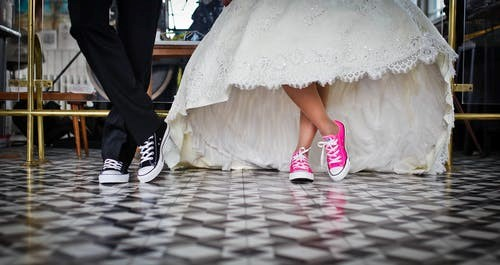 Bride wearing fun flat wedding shoes next to groom