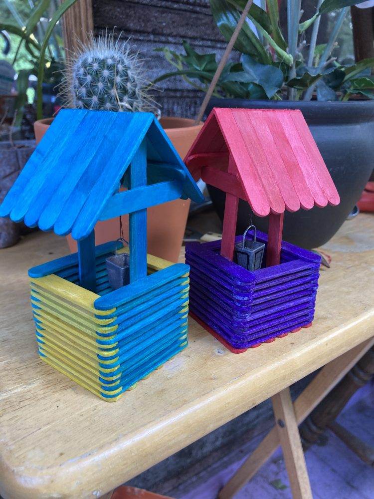 This image is of two small wishing wells made out of popsicle sticks. Their roofs are pointed and the small structures about the size of a large hand. One has a fuscia roof with a purple base and the other has a teal roof with a yellow and teal base. They have a crank and small silver buckets held by a thread