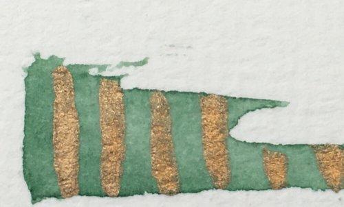 Man sieht eine Farbprobe in Gold und Smaragdgrün