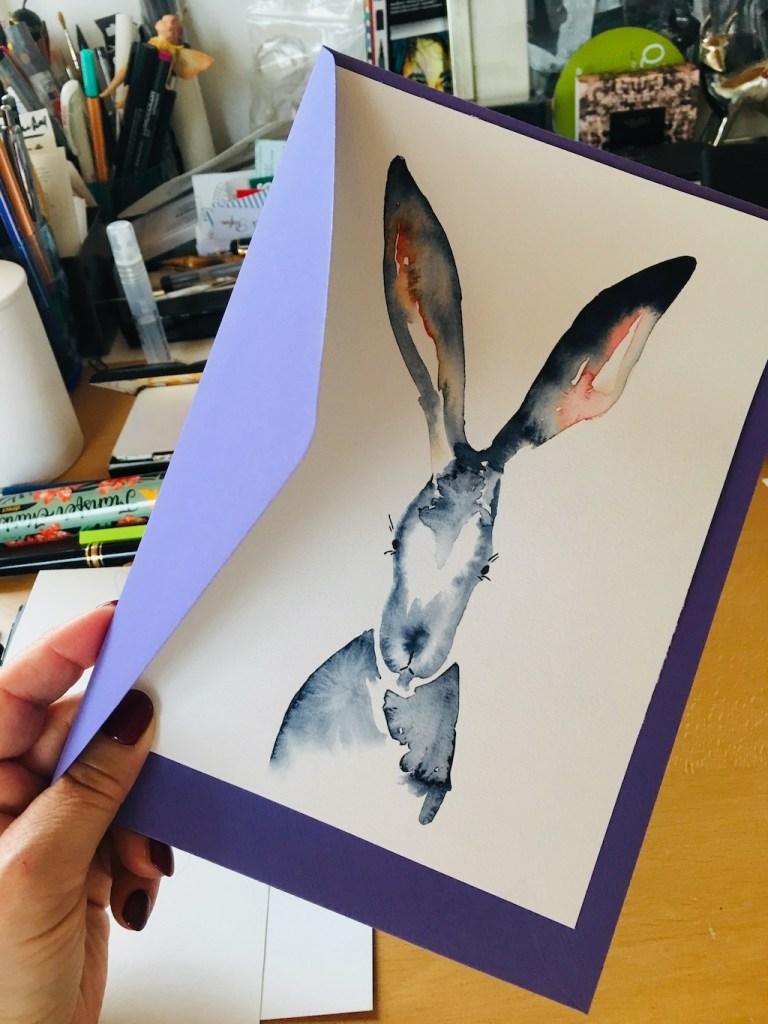 Du siehst hier, wie Dodo ein lila Kuvert mit der Osterkarte Herr Hase in die Kamera hält.