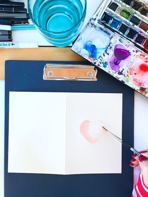 Das Bild zeigt eine Valentinskarte zum Valentinstag. Die Künstlerin Dodo Kresse hat ein Herz darauf gemalt.