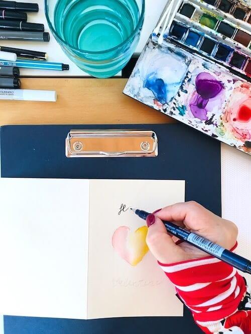 Das Bild zeigt, wie die Künstlerin Dodo Kresse eine Valentinskarte mit Letterin gestaltet.