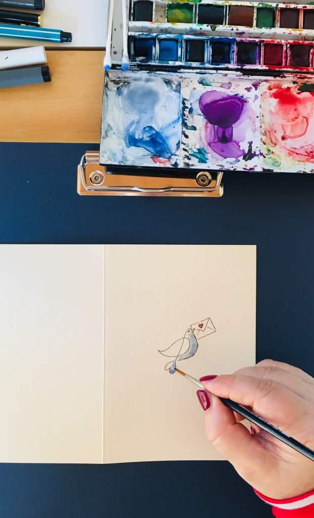 Man sieht das Einfärben der Taube auf der Valentinskarte mit Aquarellfarben, hier ein dunkles Blau.