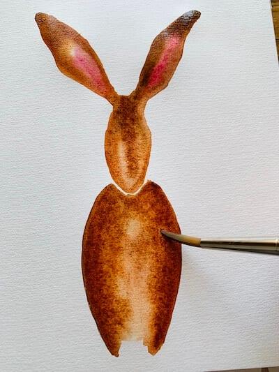 Man sieht wie die Künstlerin den Hasenkörper ausmalt
