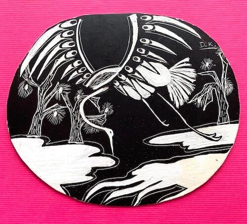 Man sieht ein Bild eines japanischen Reihers, geritzt in einem schwarzen Schabekarton von Dodo Kresse