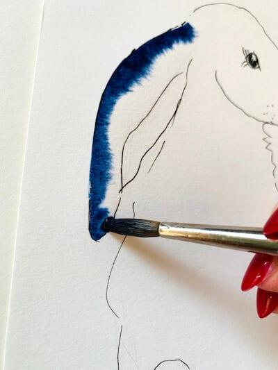 Die Farbe Indigo verläuft auf dem zuvor mit Wasser benetzen Aquarellpapier, man sieht ein Detail des Osterhasen.