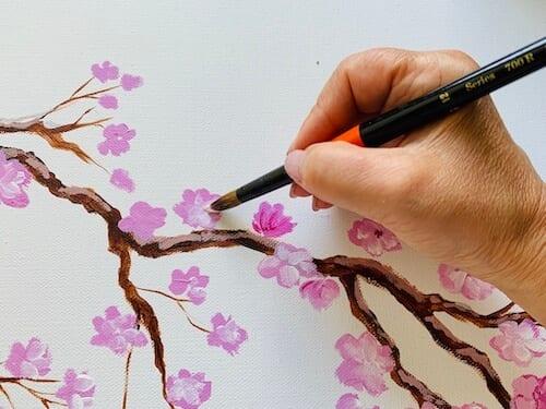Du siehst, wie ich mit weißer Acrylfarbe die Kirschblüten male