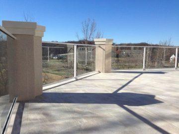 Tile deck, composite sub-floor, stucco columns, glass handrail, built in grill