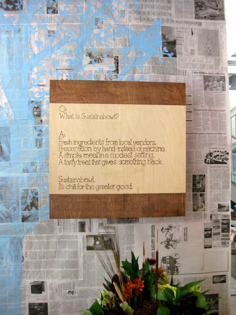 """I made our """"wallpaper"""" out of newspaper and painted a tree on it. Our mission statement was burned into a piece of plywood."""
