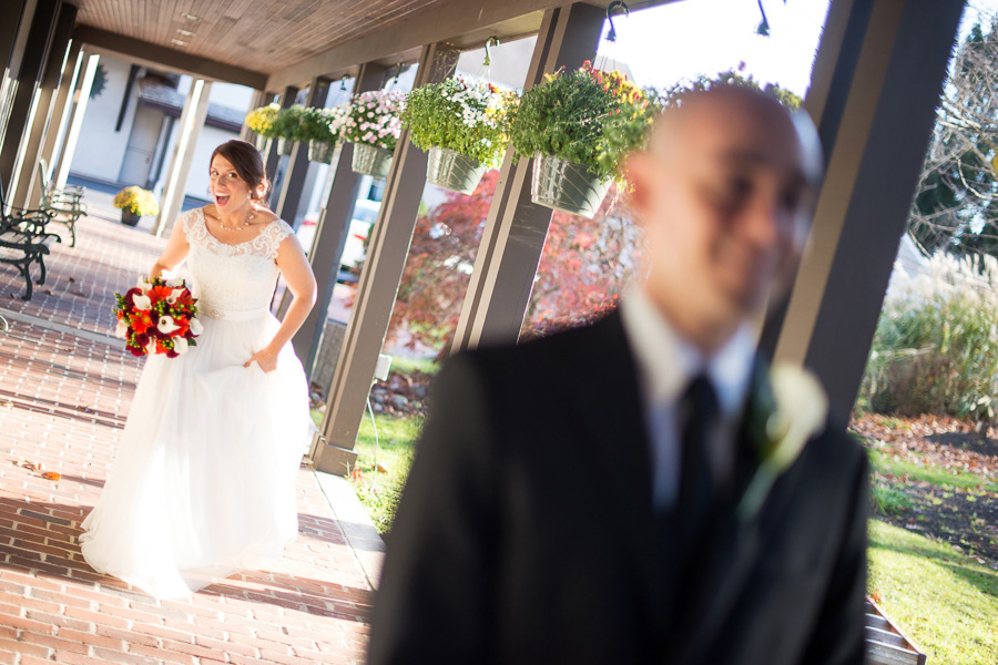 Bride laughing and sneaking up behind groom for first look at the Mendenhall Inn