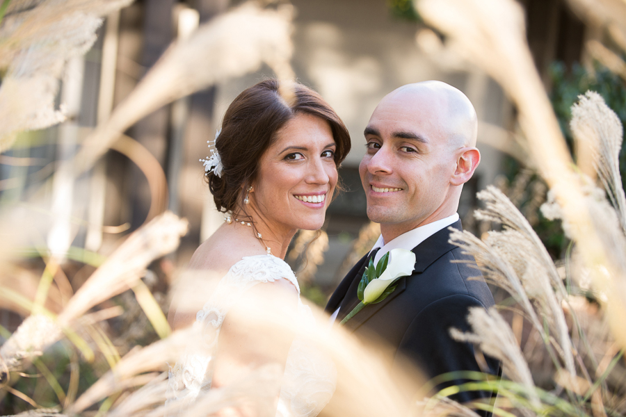 Bride and groom behind tall grass at their Mendenhall Inn wedding