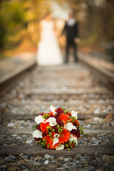 Bouquet on railroad with bride and groom in the distance at Mendenhall Inn