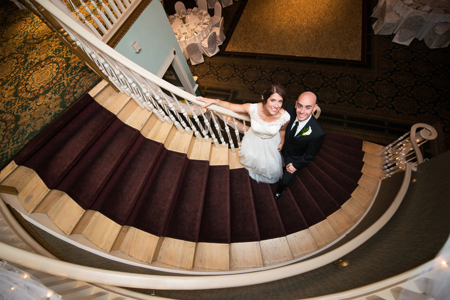 Shot from above of bride and groom on staircase at the Mendenhall Inn's Grand Ballroom