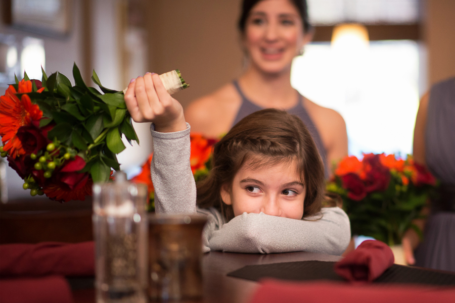 Flower girl plays with her bouquet before Mendenhall Inn wedding ceremony