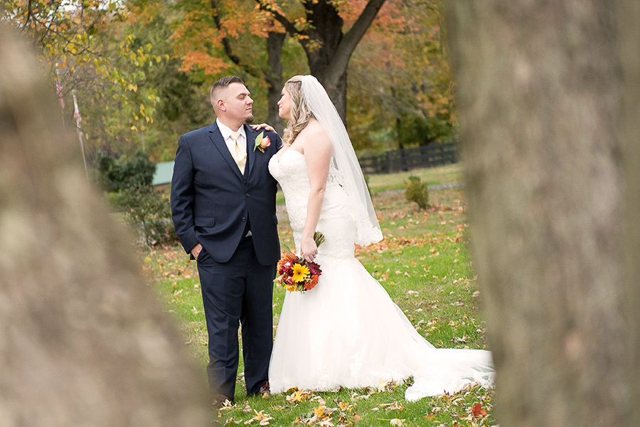 Full length shot of the bride and groom looking at one another with fall foliage in the background