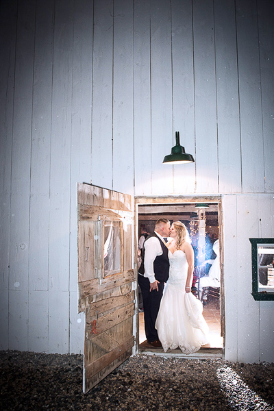 Night shot of bride and groom kissing at barn door with reception in the background