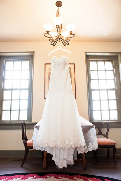 Wedding gown hanging from chandelier in historic home
