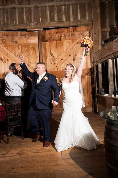 A bride and groom celebrate as the walk into their barn reception