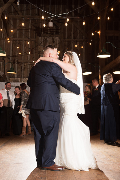 Full length of the bride and groom's first dance with lights hanging on the rafters and light behind the couple