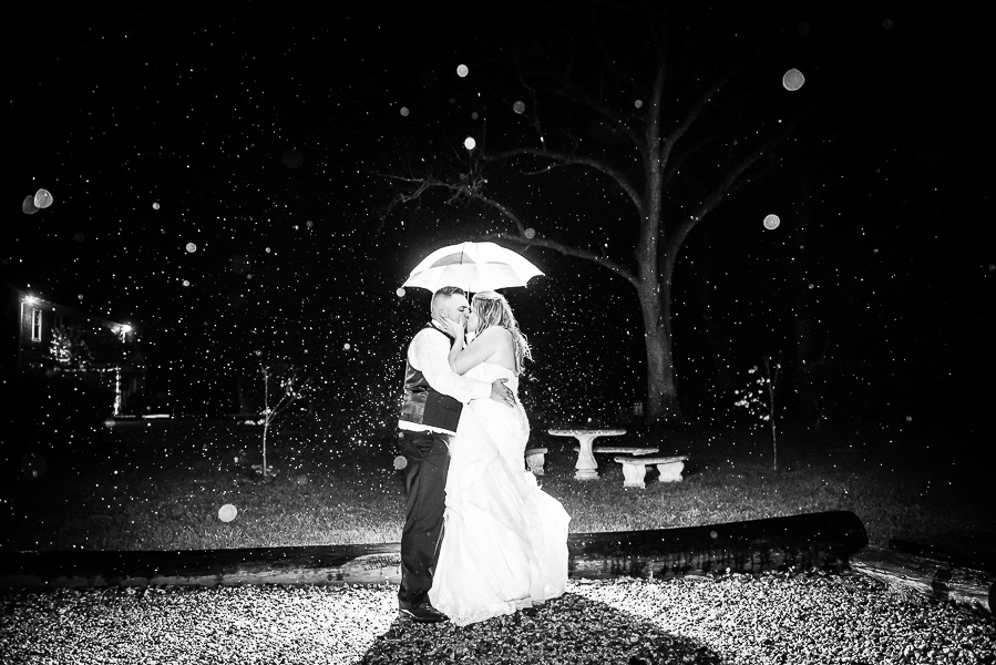 A night shot of a bride and groom kissing under an umbrella as it rains