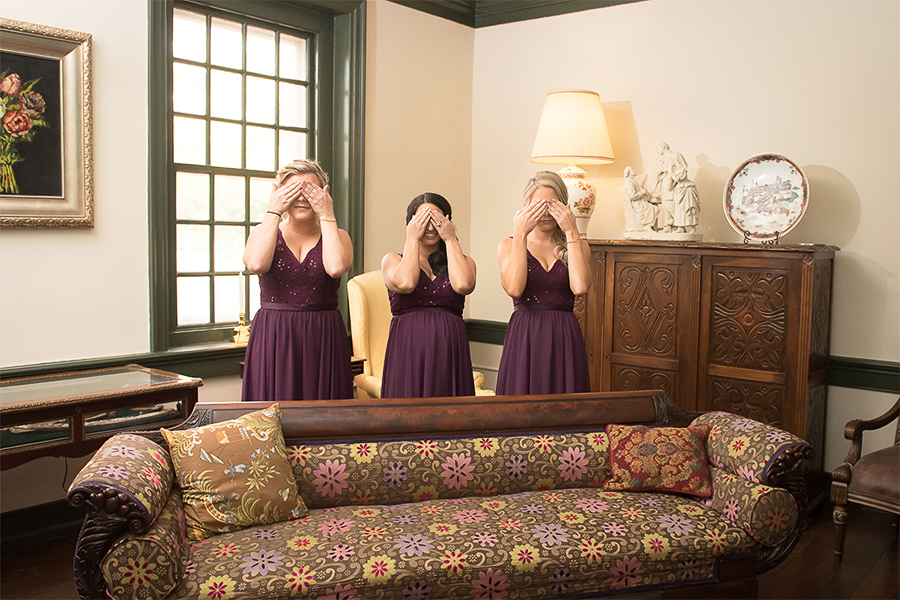 Three bridesmaids hide their eyes as they get ready to see the bride dressed and ready for the wedding