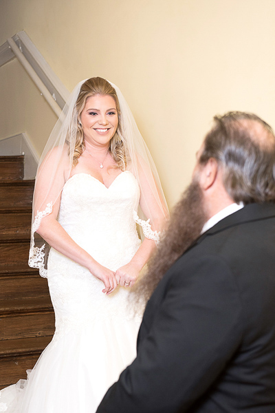 The bride walks down stairs and sees her Dad for the first time on her wedding day