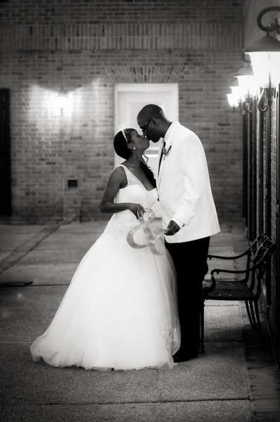 A bride and groom kiss by lamplight in the courtyard of the Hilton Christiana
