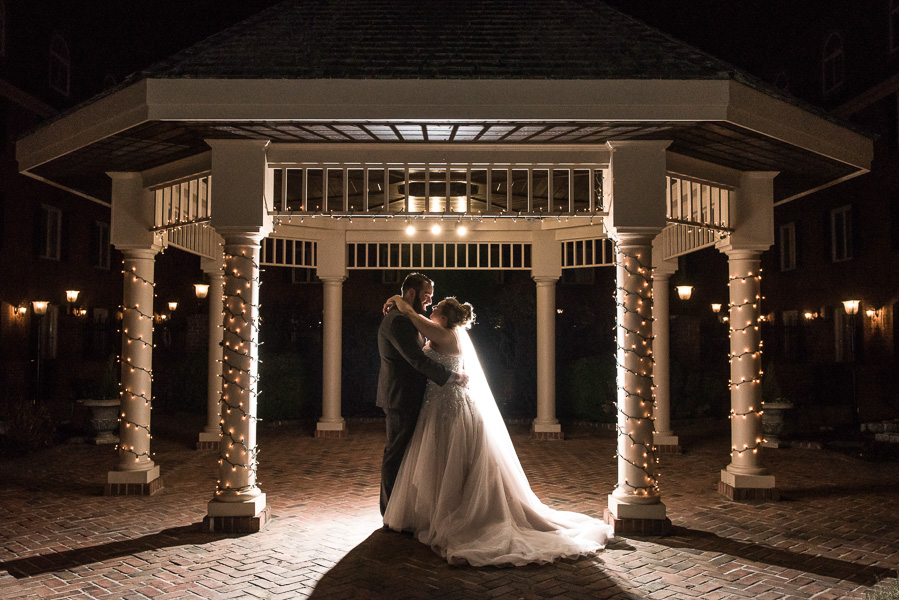 Night portrait of a bride and groom under a gazebo, light is bounced behind them for dramatic effect