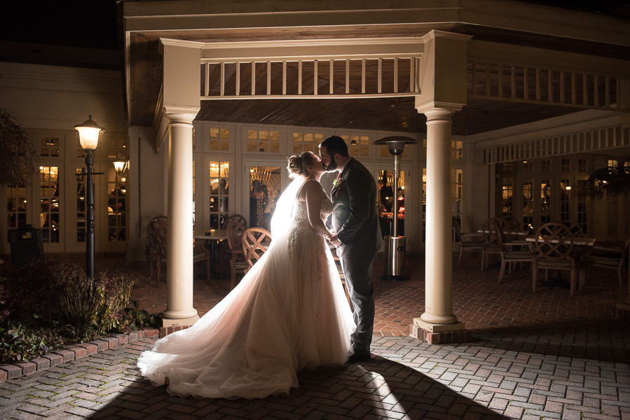 Night photo of a couple in the courtyard with glow of reception behind