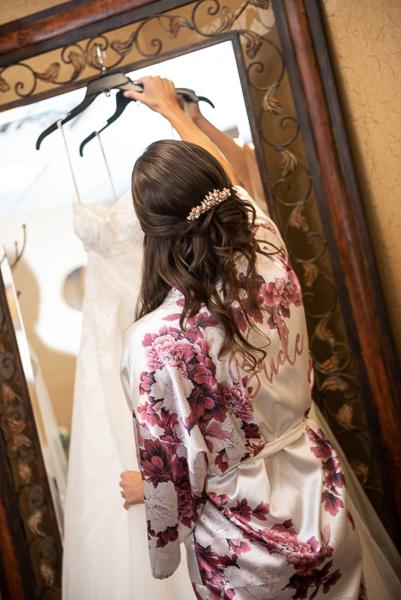 Bride in flower robe pick up her wedding gown