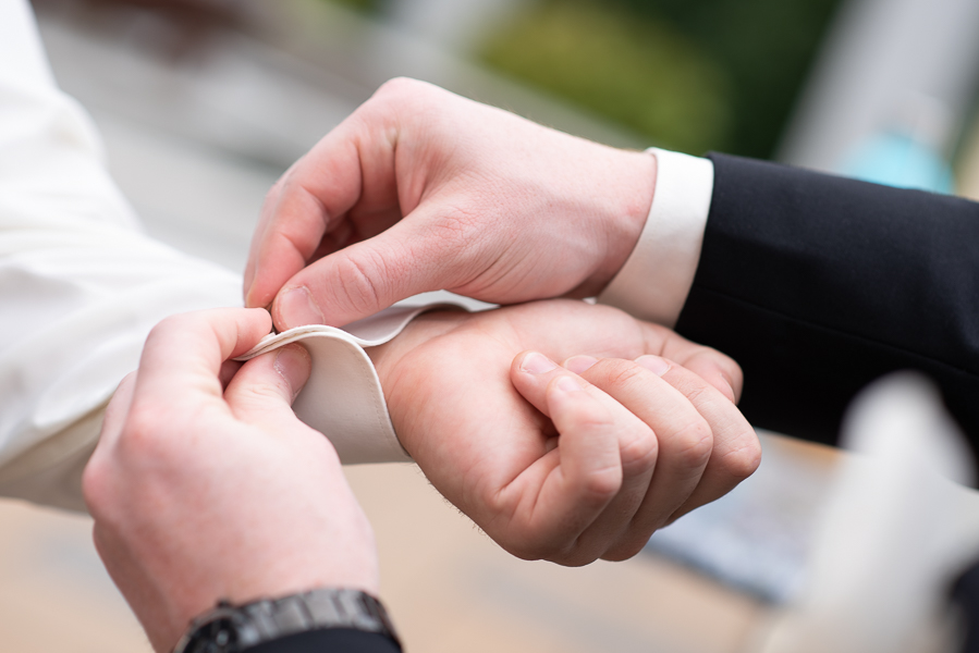 Groom gets help with his cuff links