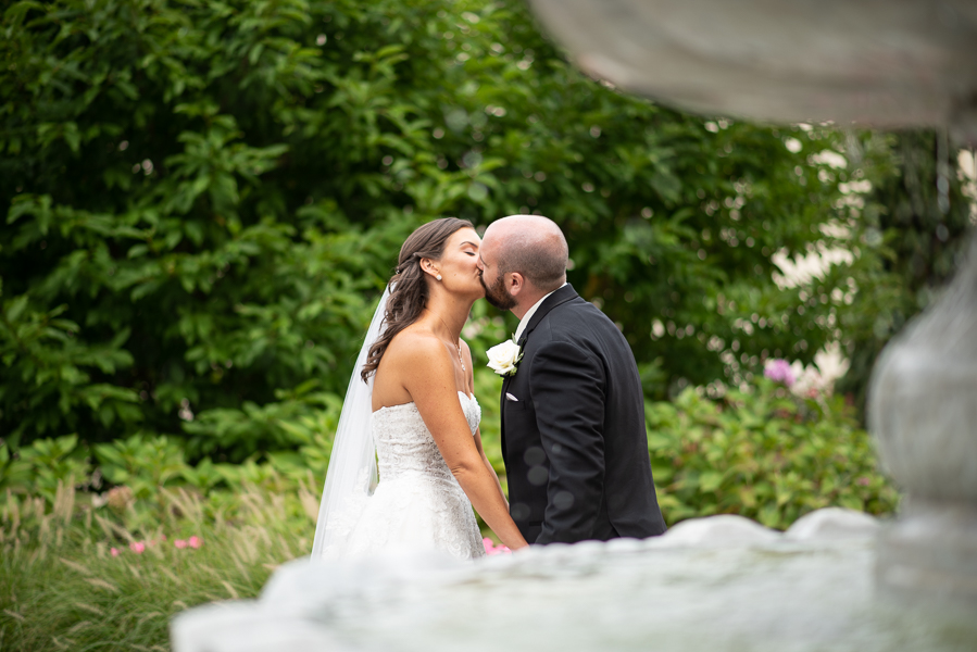 Bride and groom kissing fountain in foreground