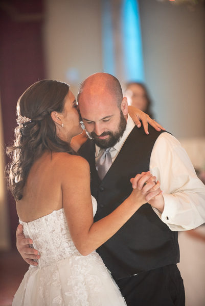 Bride whispers into grooms ear during first dance