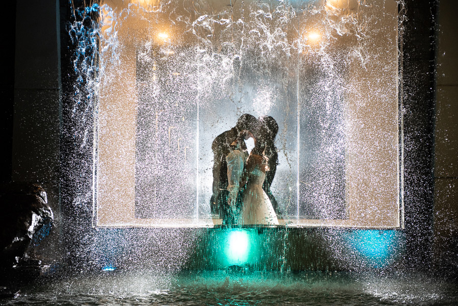 Silhouette of bride and groom behind a lighted waterfall