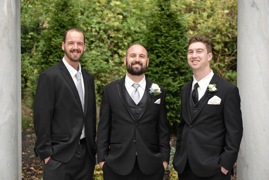 Groom and groomsmen smiling at camera
