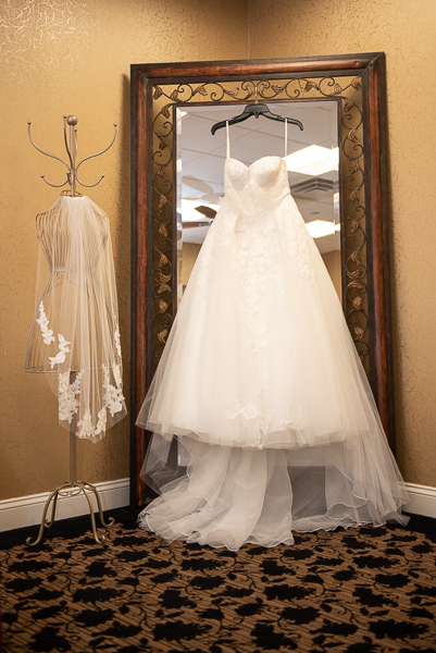 Bridal gown and veil hanging by full length mirror