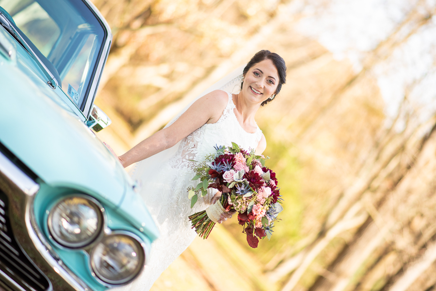 Bride poses with old turquoise car before reception at The Farmhouse in Delaware
