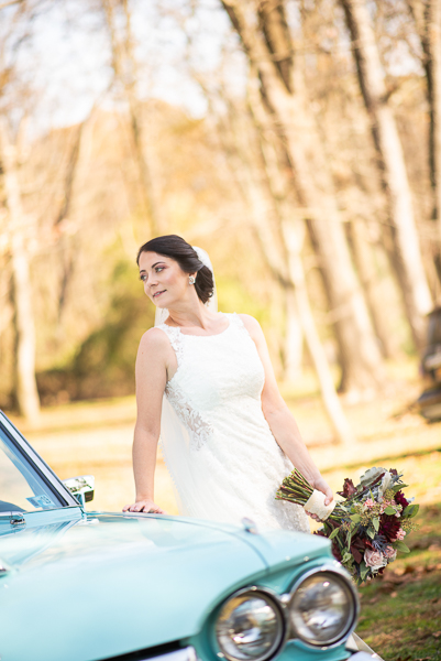 Bride poses by old car before reception at The Farmhouse in Delaware