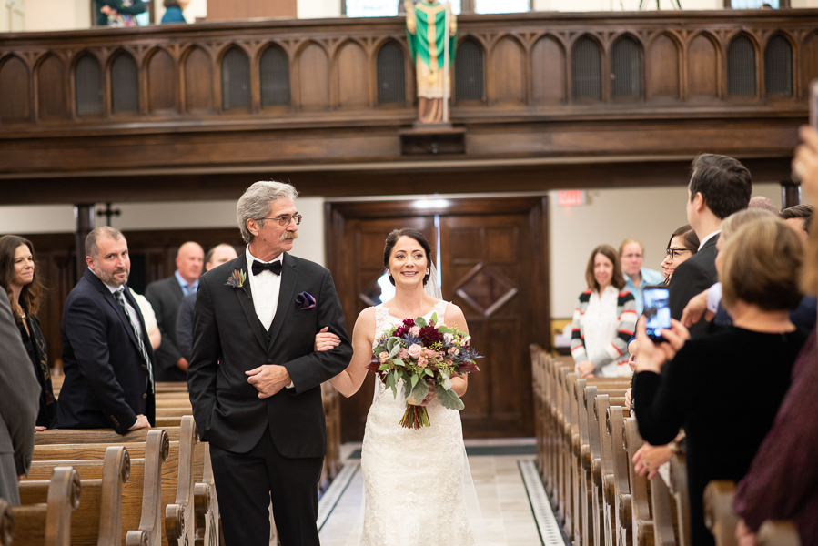 The bride smiles at guests as her father walks her down the aisle