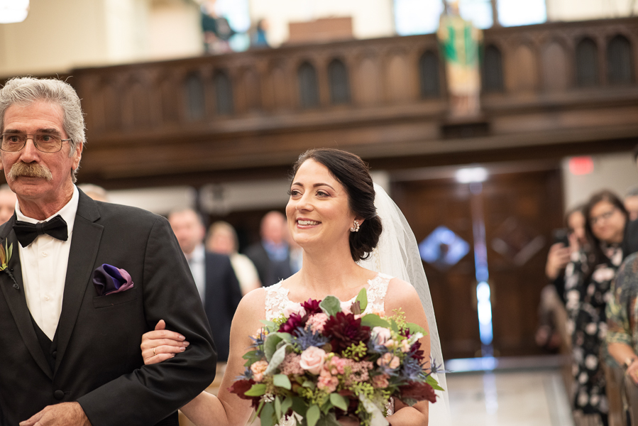 Bride smiles at the groom as her dad walks her down the aisle