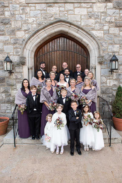 Bridal party group shot outside on church steps in front of beautiful brown door before reception at The Farmhouse in Delaware