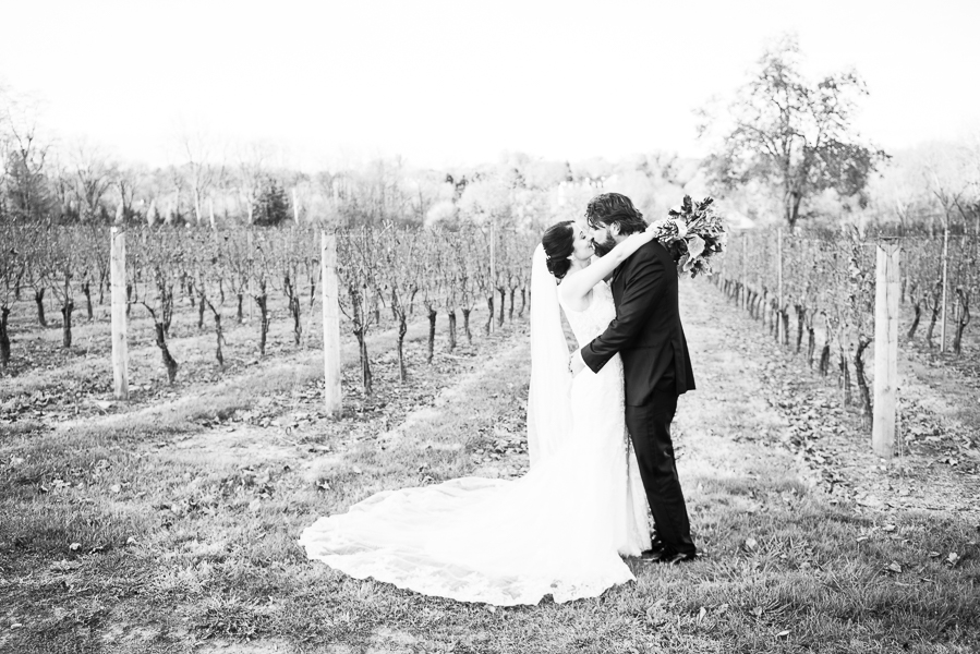 Black and white full length photo of bride and groom kissing in front of the vineyards at Galer Estate Winery