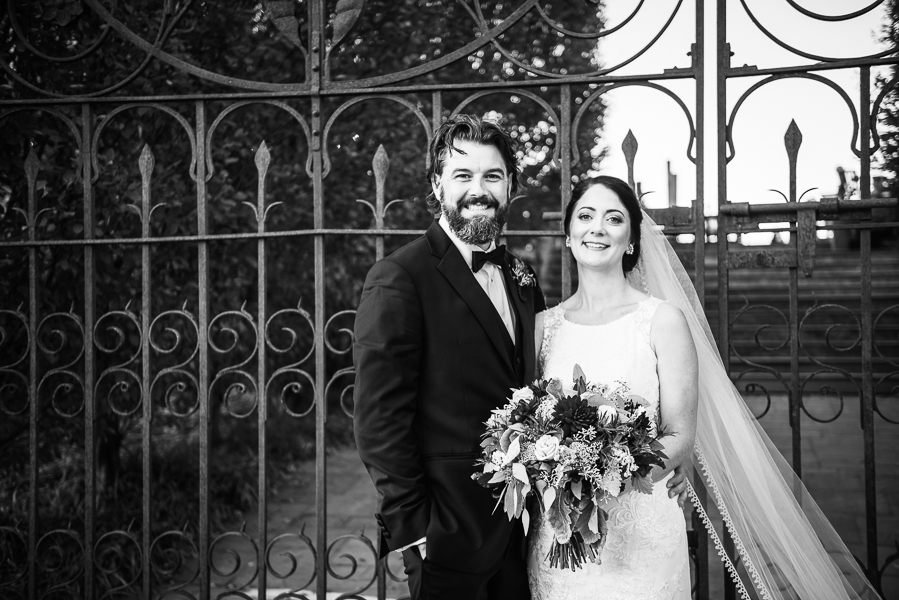Black and white photo of bride and groom standing in front of beautiful iron gates at Galer Estate Winery